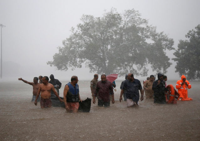 Members of a rescue team wade through a water-logged area during heavy rains on the outskirts of Kochi in the southern state of Kerala, India, August 8, 2019.