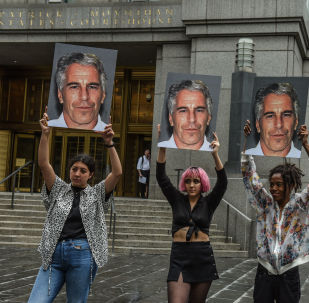 In this file photo taken on July 8, 2019, a protest group called Hot Mess hold up photos of Jeffrey Epstein in front of the Federal courthouse on July 8, 2019 in New York City.