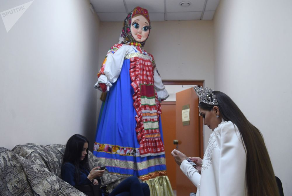 A participant in white is seen texting in a back room standing next to a human-sized doll dressed in traditional Russian attire.