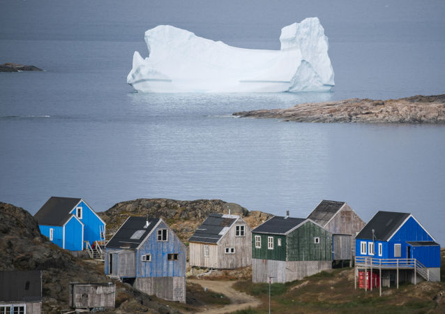 Icebergs float behind the town of Kulusuk in Greenland on August 19, 2019.