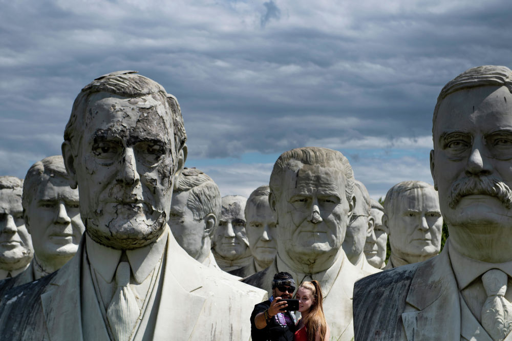 A couple poses for a selfie with giant salvaged busts of former US Presidents August 25, 2019, in Williamsburg, Virginia.