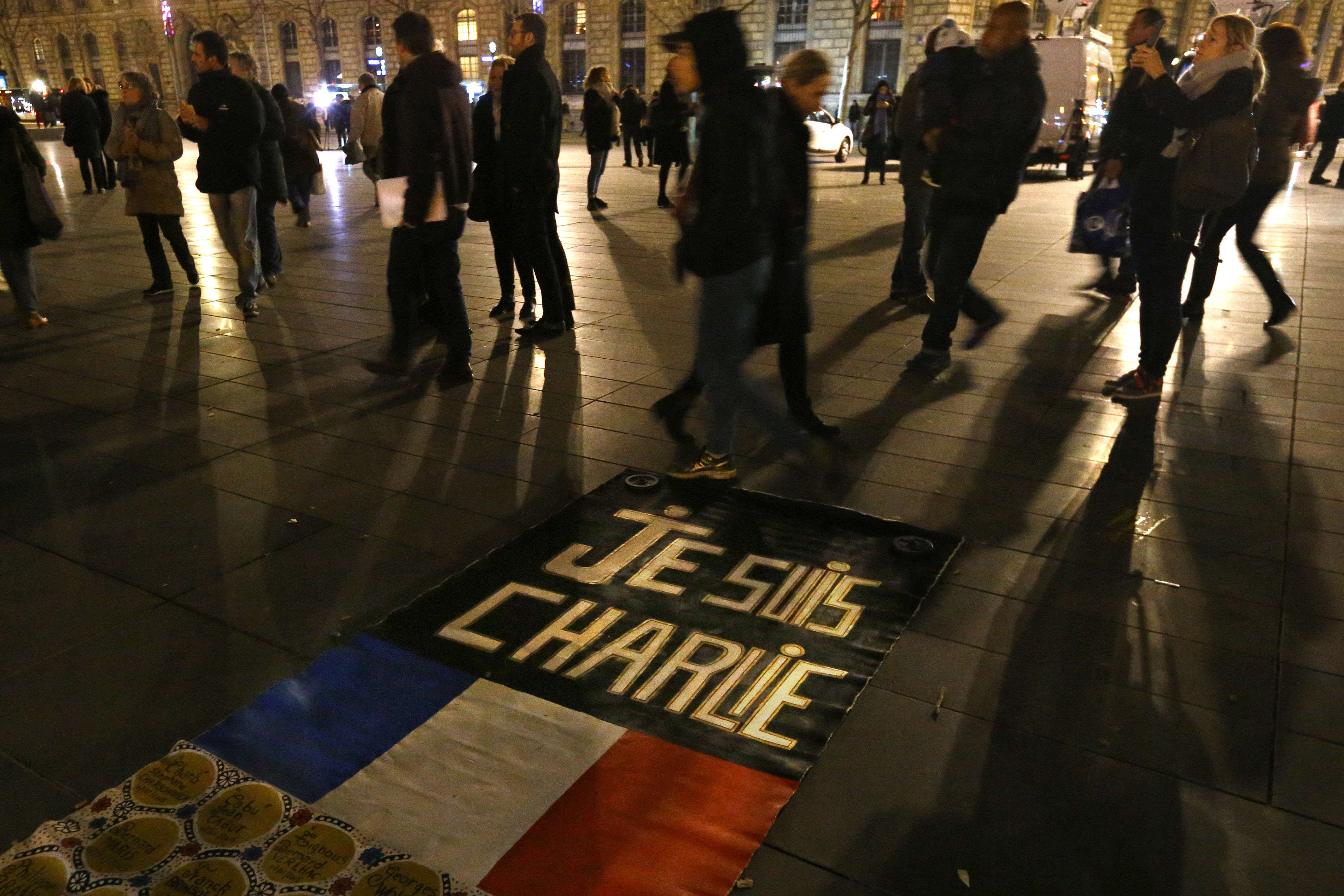 People walk around to banner reading Je suis Charlie, I am Charlie on the Place de la Republique during a gathering that marks one year after the attacks on Charlie Hebdo satirical newspaper, in Paris, France, Thursday, Jan. 7, 2016.