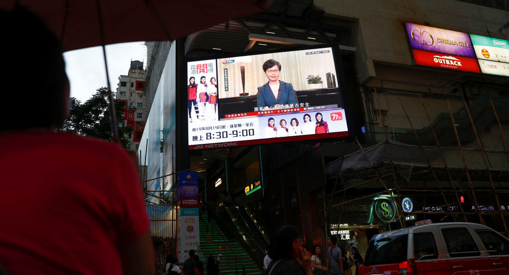 People watch a news conference of Hong Kong's Chief Executive Carrie Lam televised on a big screen in a shopping mall in Hong Kong