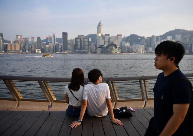 Visitors look at the view along Victoria Harbour in Hong Kong on August 22, 2019.