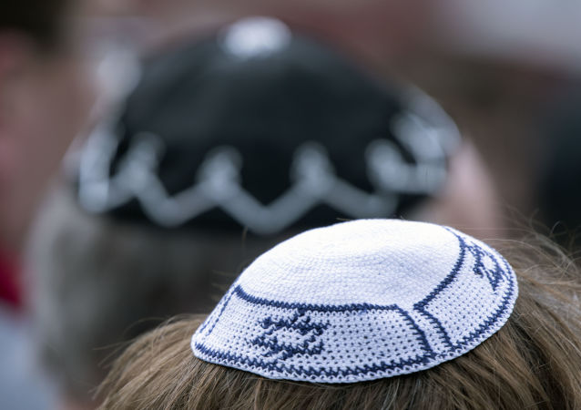 People of different faiths wear the Jewish kippah during a demonstration against antisemitism in Germany in Erfurt, Germany, Wednesday, April 25, 2018.