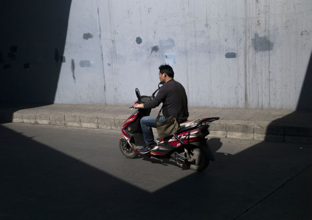 A man rides his electric scooter close to the fourth ring road in Beijing on April 20, 2016