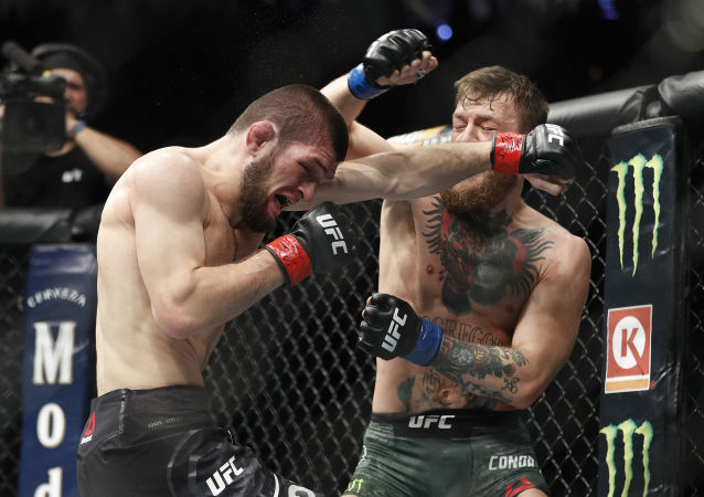 Khabib Nurmagomedov, left, and Conor McGregor throw punches during a lightweight title mixed martial arts bout at UFC 229 in Las Vegas, Saturday, Oct. 6, 2018