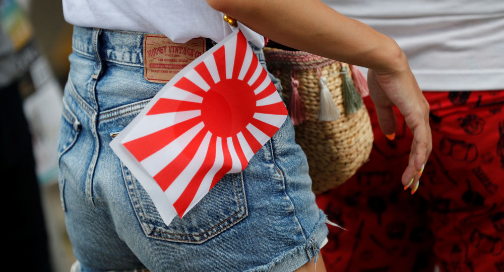 A woman carries an Imperial Japanese flag as she visits the Yasukuni Shrine in Tokyo, Japan August 15, 2019, on the 74th anniversary of Japan's surrender in World War Two.
