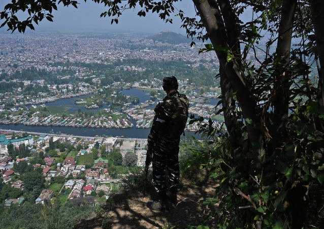 An Indian paramilitary trooper patrols at the top of a hill in Srinagar on August 25, 2019