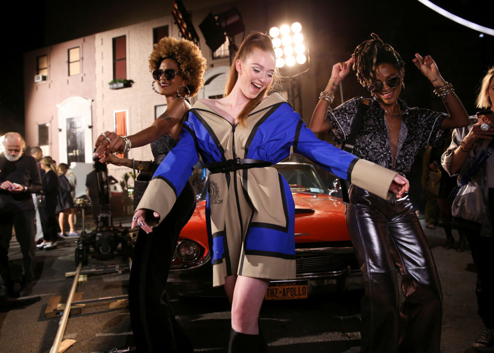 Models dance in front of a car before the Tommy Hilfiger TommyNow Fall runway show at the Apollo Theater during New York Fashion Week in New York, U.S., September 8, 2019.