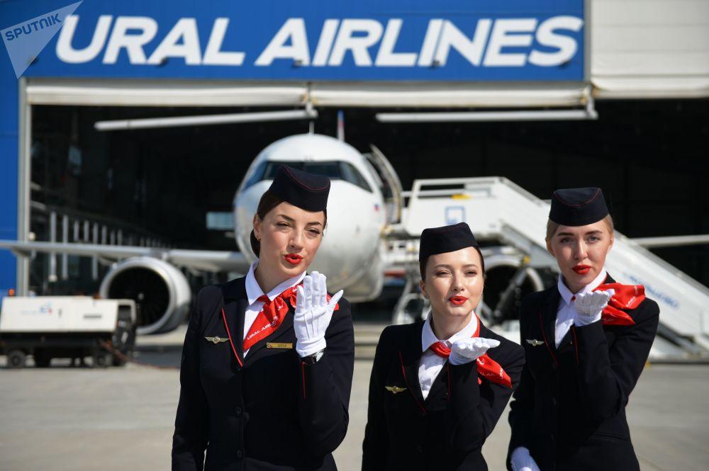 Flight attendants pose for photos at Koltsovo airport in Yekaterinburg during the presentation of a new Airbus A320neo plane purchased by Ural Airlines