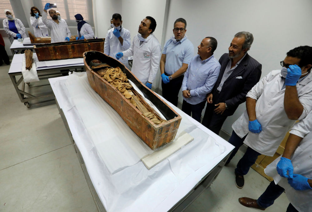 Egyptian Minister of Antiquities Khaled El-Enany (C) and archaeologists look at the pharaonic mummy of Sennedjem  after it was removed from his coffin at the National Museum of Egyptian Civilization in Cairo