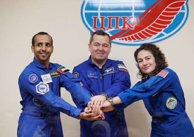 Crew members Jessica Meir of the US, Oleg Skripochka of Russia and Hazzaa Ali Almansoori of the United Arab Emirates pose for a picture behind a glass wall during a final news conference ahead of their mission to the International Space Station (ISS) in Baikonur, Kazakhstan, 24 September 2019