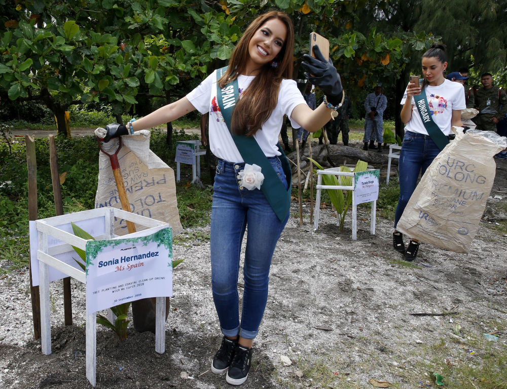 Sonia Romeo, left, of Spain and Tunde Blaga of Hungary, candidates for the Miss Earth 2019 beauty pageant, take selfies prior to taking part in a coastal cleanup, one of the activities lined up to call the attention to help save Mother Earth, Monday, Sept. 30, 2019 in suburban Las Pinas city, south of Manila, Philippines.
