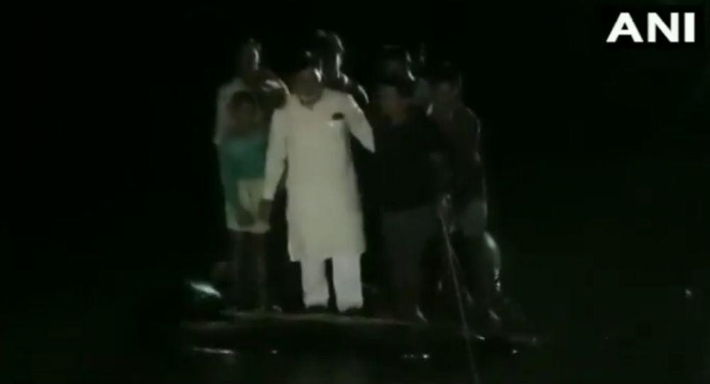 BJP MP Ram Kripal Yadav falls into the water after the makeshift boat he was in, capsized in Masaurhi, Patna district, during his visit to the flood affected areas yesterday