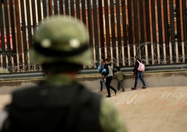 National Guard soldier observes migrants after crossing illegally into El Paso, Texas, U.S. to turn themselves in to U.S. Border Patrol agents to ask for asylum, as seen from Ciudad Juarez