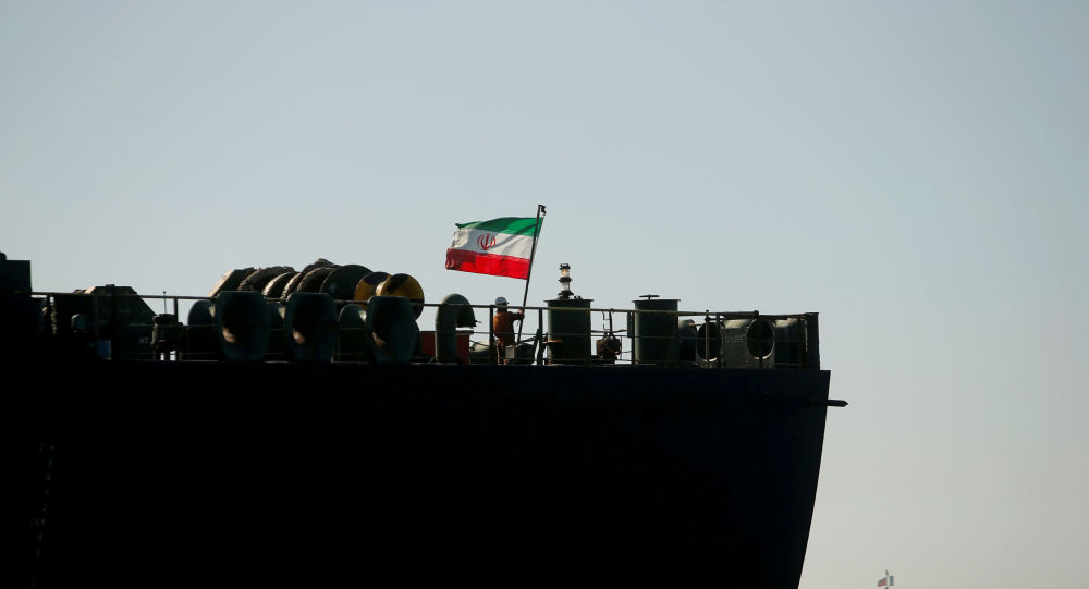 A crew member raises the Iranian flag on the Iranian oil tanker Adrian Darya 1, formerly named Grace 1, as it sits anchored after the Supreme Court of the British territory lifted its detention order, in the Strait of Gibraltar, Spain, 18 August 2019.