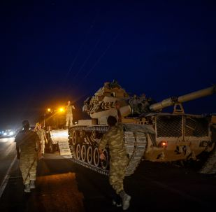 A Turkish army's tank drives down from a truck as Turkish armed forces drive towards the border with Syria near Akcakale in Sanliurfa province on October 8, 2019