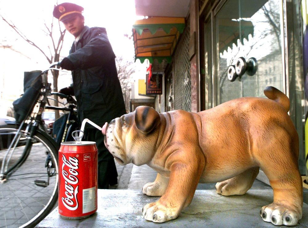 A Chinese postal worker leaves with his bike after delivering mail to a fashion salon decorated with a porcelain dog drinking a US soda out of a straw 16 February 2000 in Beijing.