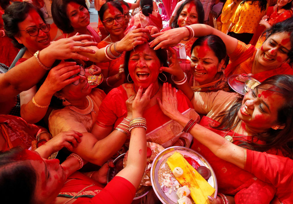 A Hindu woman reacts as Sindhur, or vermillion powder, is applied to her face after worshipping an idol of the Hindu goddess Durga on the last day of the Durga Puja festival in Chandigarh, India, October 8, 2019.
