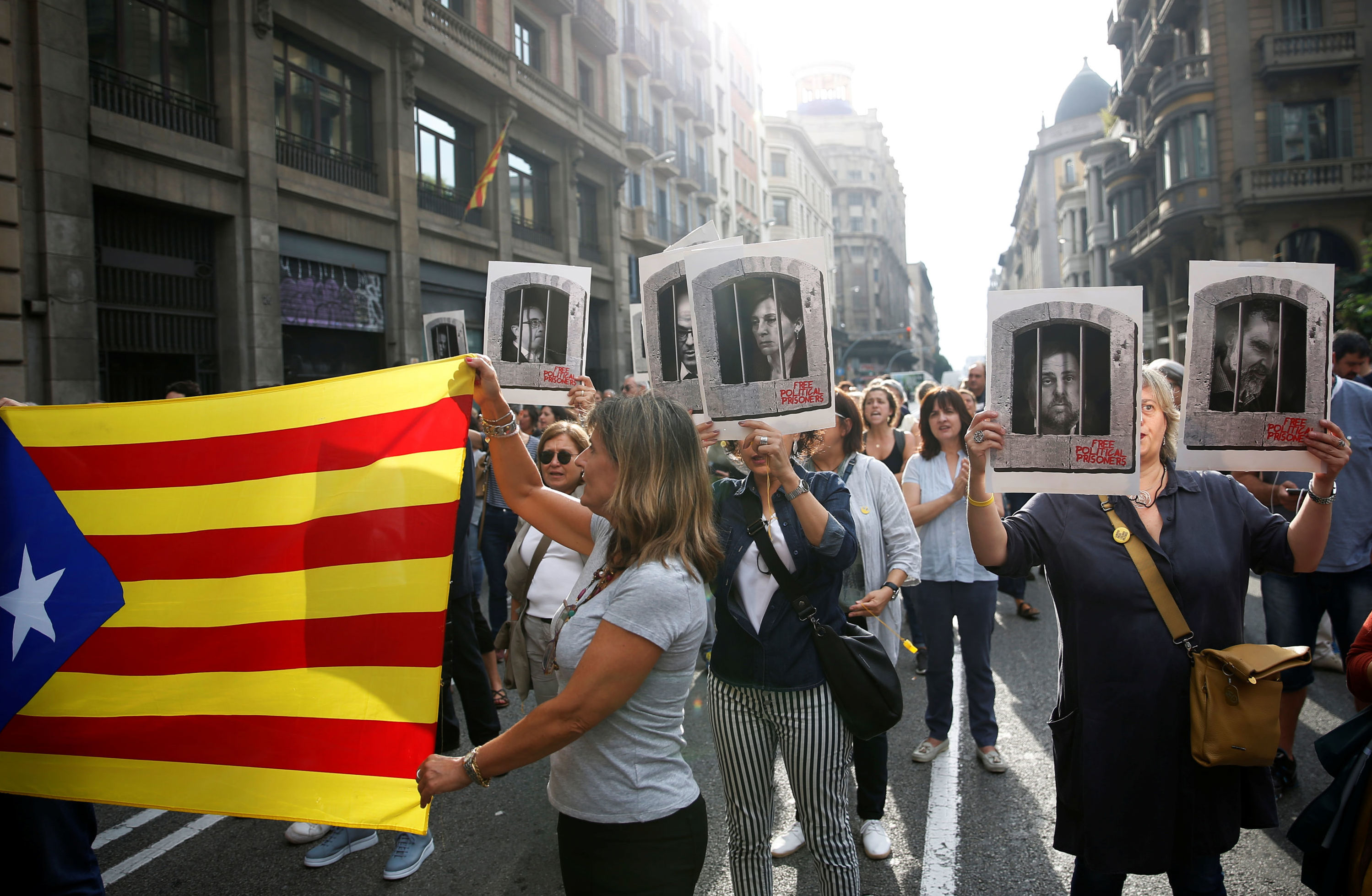 People holding an Estelada (Catalan separatist flag) and pictures of Catalan politicians as they walk through Via Laetana Avenue during a protest after a verdict in a trial over a banned independence referendum, in Barcelona, Spain October 14, 2019