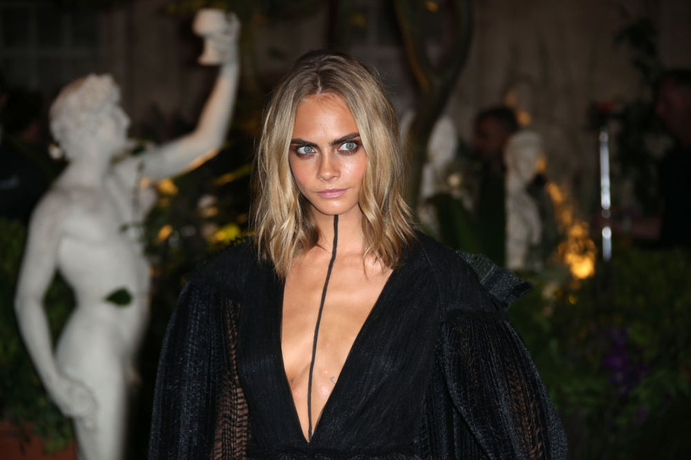 Model Cara Delevingne poses for photographers upon arrival at the Burberry Spring/Summer 2017 fashion show at London Fashion Week in London, Monday, Sept. 19, 2016.