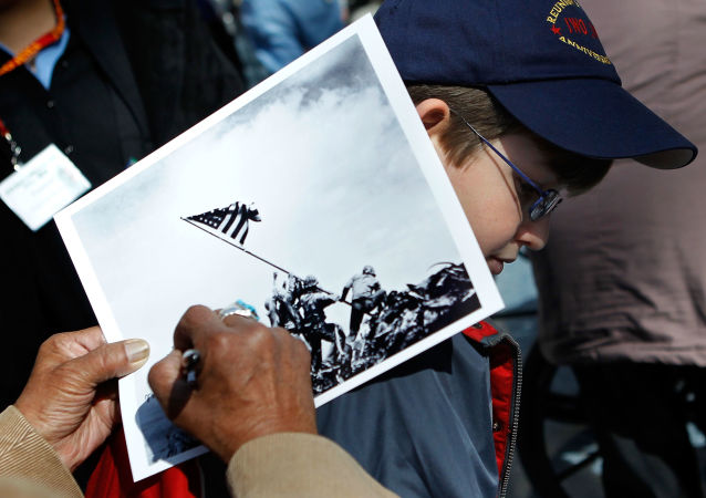 An Iwo Jima veteran signs autograph on the famous WWII photograph Raising the Flag on Iwo Jima shot by AP photographer Joe Rosenthal for Michael Scott of Altoona, Pennsylvania, at a ceremony to mark the 65th anniversary of the battle of Iwo Jima February 19, 2010 at the National Museum of Marine Corps in Triangle, Virginia