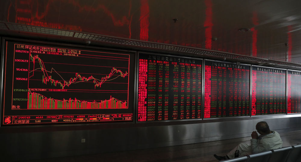 An investor sits near an electronic board displaying stock prices at a brokerage house in Beijing, Wednesday, Oct. 16, 2019.