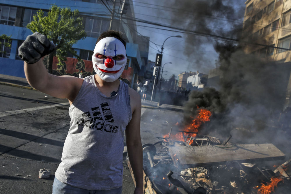 A masked demonstrator raises his clenched fist at a burning barricade during protests in Valparaiso, Chile, on October 20, 2019.