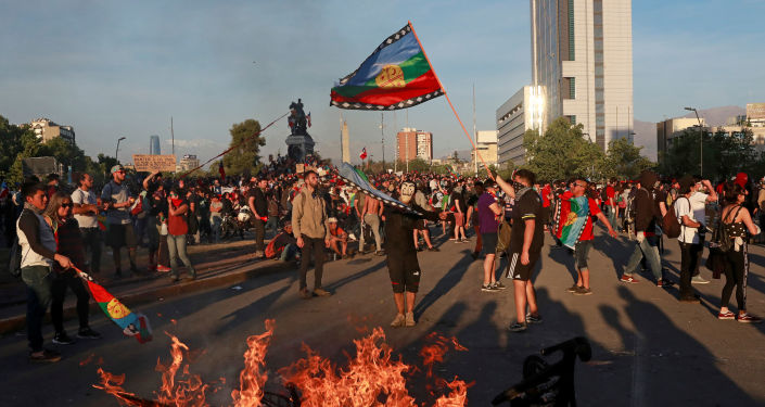 Demonstrators wave a Mapuche flag during a protest against Chile's state economic model in Santiago, Chile, 26 October 2019