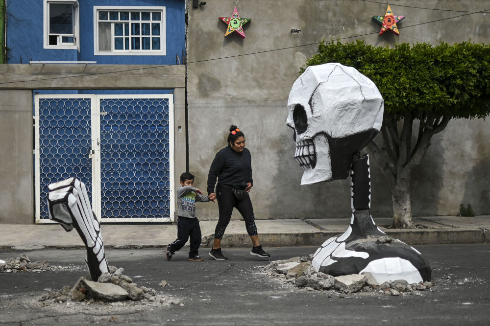 A woman and a child walk next to a huge cardboard skull made by artisans in a street in the Tlahuac neighbourhood, in Mexico City on October 28, 2019, ahead of the Day of the Dead celebrations.