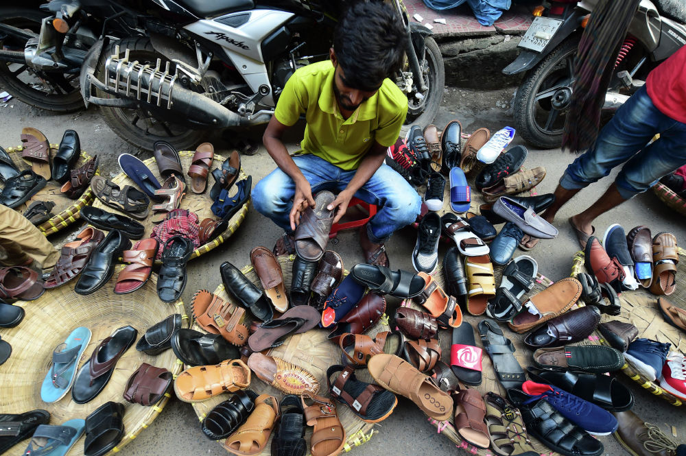 A Bangladeshi street shoe vendor arranges shoes as he prepares his display in Dhaka on October 30, 2019.