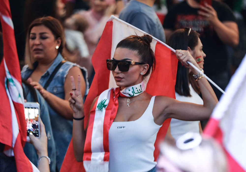 A Lebanese demonstrator waves a national flag at the Martyrs' Square in the centre of the capital Beirut on October 27, 2019, during ongoing anti-government protests.
