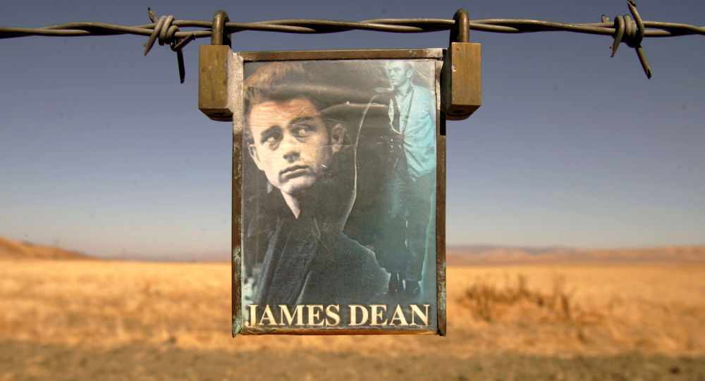 A portrait of U.S. actor James Dean hangs from a fence near the intersection of Highways 46 and 41 near Cholame, California September 30, 2005