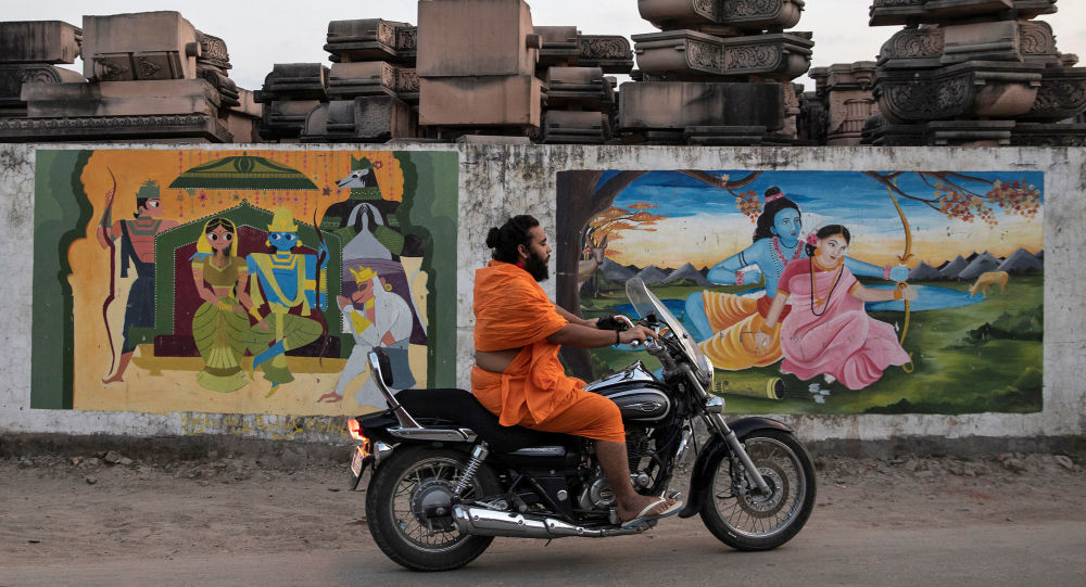 A Hindu priest rides past a workshop where the pillars that Hindu nationalist group Vishva Hindu Parishad (VHP) say will be used to build a Ram temple at the disputed religious site are kept, in Ayodhya, India, 22 October 2019