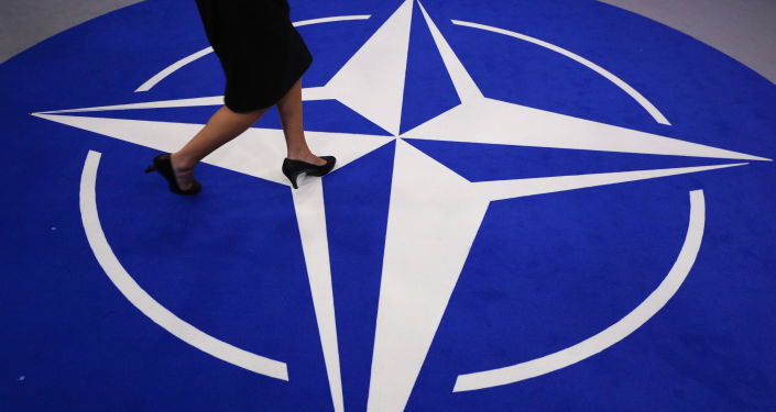 A woman walks across a carpet with the NATO logo ahead of the NATO (North Atlantic Treaty Organization) summit, at the NATO headquarters in Brussels, on July 11, 2018