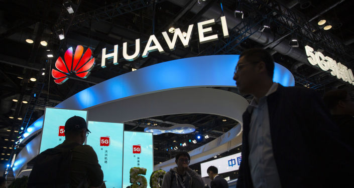 Attendees walk past a display for 5G services from Chinese technology firm Huawei at the PT Expo in Beijing, Thursday, Oct. 31, 2019