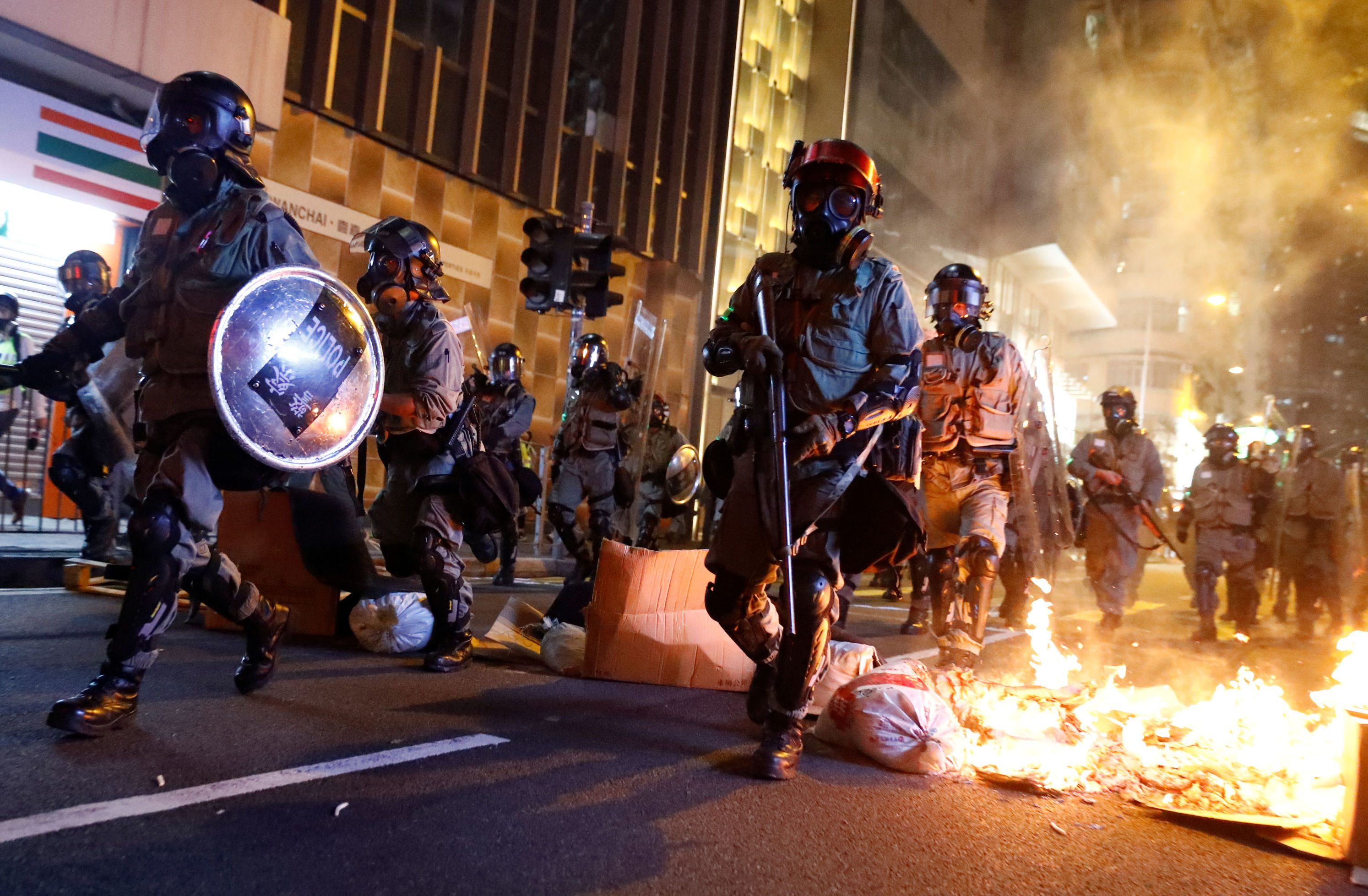 Police passes a burning barricade to break up thousands of anti-government protesters during a march billed as a global emergency call for autonomy, in Hong Kong, China November 2, 2019