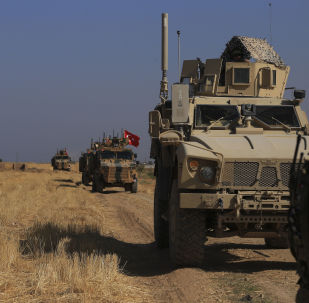 FILE - This Friday, Oct. 4, 2019 file photo, Turkish and American armored vehicles patrol as they conduct joint ground patrol in the so-called safe zone on the Syrian side of the border with Turkey, near the town of Tal Abyad, northeastern Syria