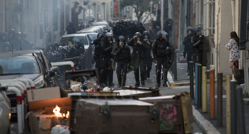 Police approach a barricade made by protesters during a yellow vest demonstration marking the one year anniversary of the movement in Marseille, southern France, Saturday, Nov. 16, 2019.  Police are deployed around key sites in Paris as France's yellow vest protesters prepare to mark the first anniversary of their sometimes-violent movement for economic justice.
