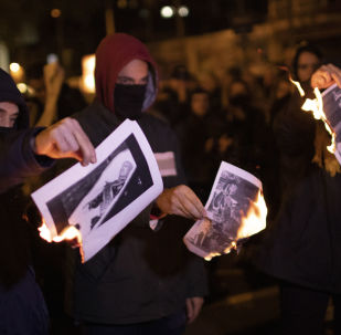 People burn photos of late Spanish dictator Gen. Francisco Franco during a demonstration in Barcelona, Spain Thursday, Oct. 24, 2019.