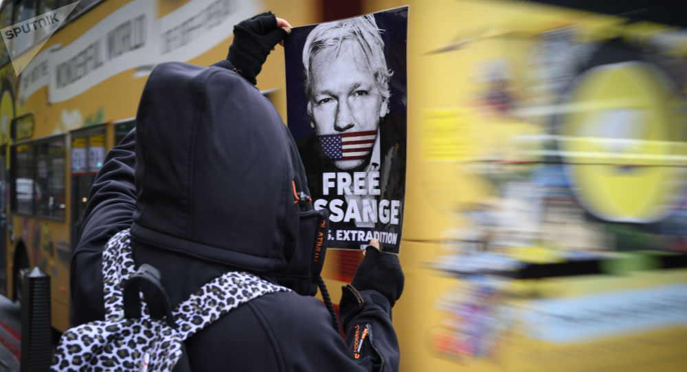 A protester holds a leaflet demanding the release of Julian Assange