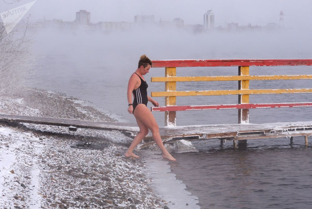 A woman prepares to open the season of ice water swimming in the Yenisey River in Krasnoyarsk
