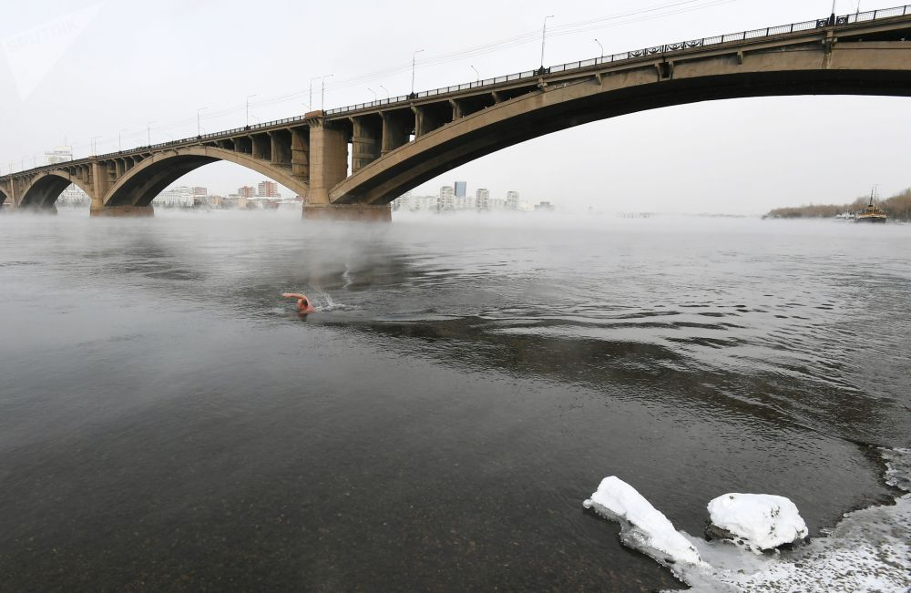 A man swims during the opening of the cold water swimming season in Krasnoyarsk