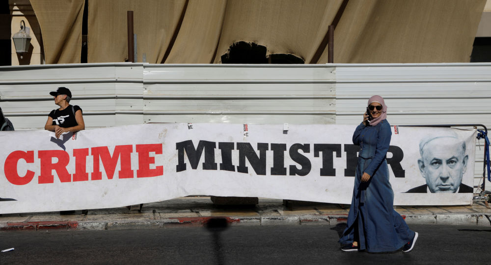 A woman walks past a banner depicting Israeli Prime Minister Benjamin Netanyahu and the words Crime Minister outside the Justice Ministry
