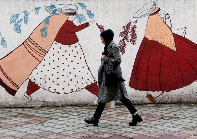 An Iranian woman walks past an artistic mural in Tehran