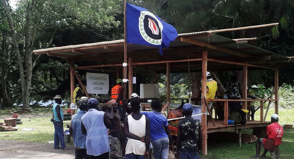 Residents hold a Bougainville flag at a polling station during a non-binding independence referendum in Arawa, on the Papua New Guinea island of Bougainville November 26, 2019