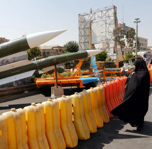 An Iranian woman looks at Taer-2 missile during a street exhibition by Iran's army and paramilitary Revolutionary Guard celebrating  Defence Week marking the 39th anniversary of the start of 1980-88 Iran-Iraq war, at the Baharestan Square in Tehran, on September 26, 2019