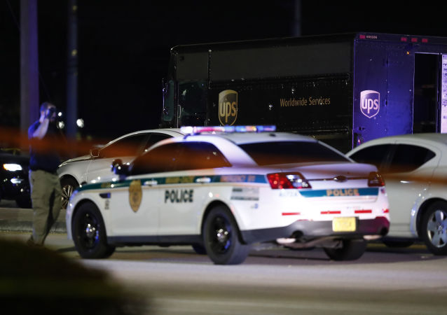 Authorities walk near a UPS truck and other vehicles at the scene of a shooting, Thursday, Dec. 5, 2019, in Miramar, Fla.