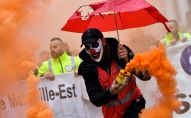 A man wearing a clown mask and waving a smoke bomb takes part in a demonstration to protest against the pension overhauls, in Marseille, southern France, on December 5, 2019 as part of a national general strike.
